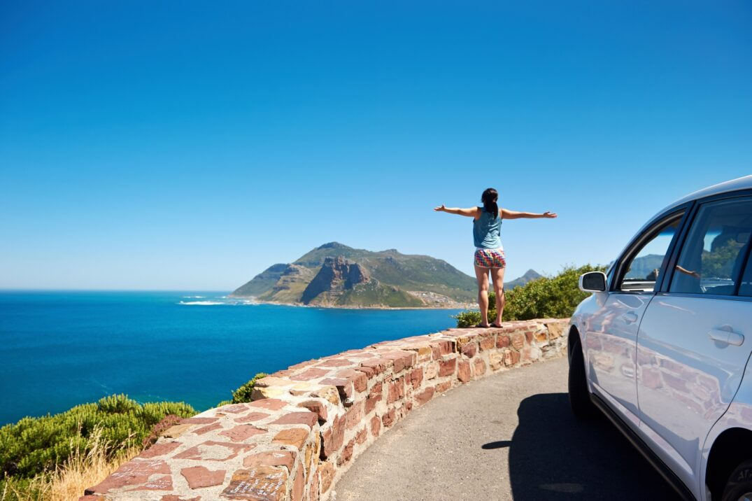 17636541 - carefree tourist stands on chapmans peak drive with arms outstretched in freedom girl pose with rental car